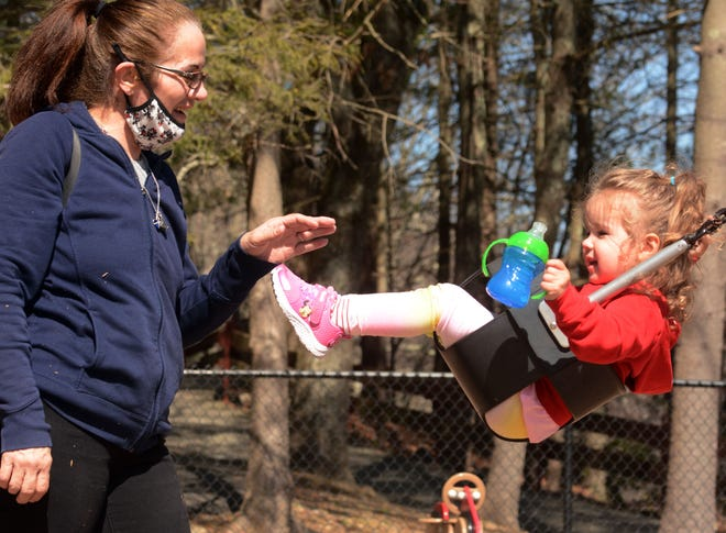 """Arvia Lassu pushes a swing for her granddaughter, Valentina Marchenkoff, 2, both of Moosup, Monday during the second day of spring at Mohegan Park in Norwich. More spring weather and temperatures in the low 60s is predicted today. Asked about the mild weather Lassu said. """"It's about time."""""""