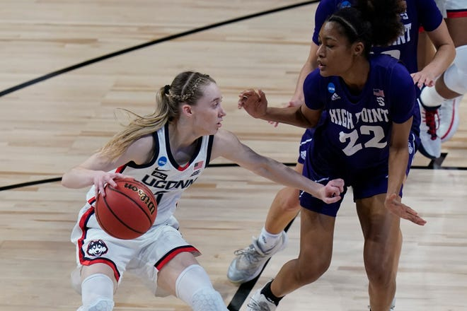 UConn guard Paige Bueckers (5) drives against High Point guard Chyna McMichel (22) during the first half of a college basketball game in the first round of the women's NCAA tournament at the Alamodome in San Antonio, Sunday, March 21, 2021.