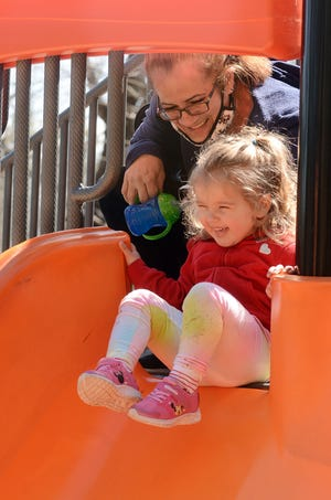 """Arvia Lassu starts a countdown for her granddaughter, Valentina Marchenkoff, 2, both of Moosup, before she goes down a slide Monday during the second day of spring at Mohegan Park in Norwich. More spring weather and temperatures in the low 60s is predicted today. Asked about the mild weather Lassu said. """"It's about time."""""""