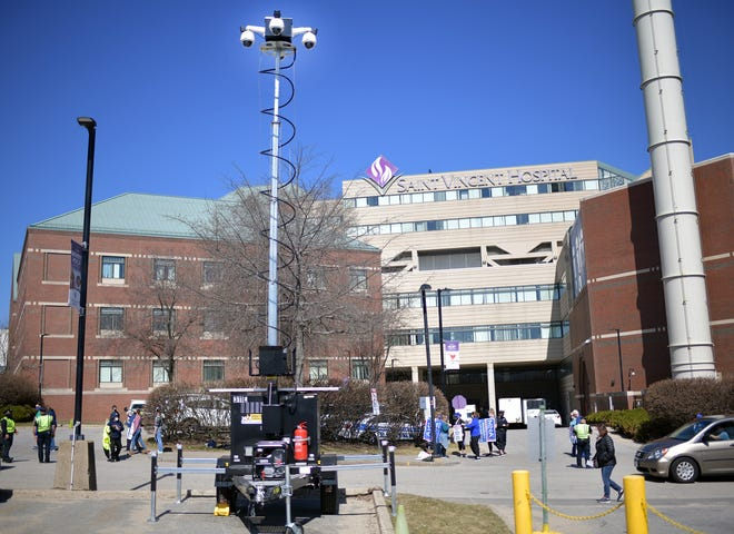 A portable camera tower at the edge of a parking lot outside St. Vincent Hospital in Worcester, across from a loading dock area where striking nurses walk the picket line.