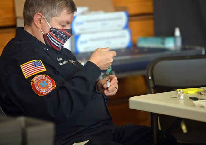 Melissa Blodgett, a captain with the Uxbridge Fire Department, draws a vaccine in Uxbridge at a regional collaborative vaccination center last month.