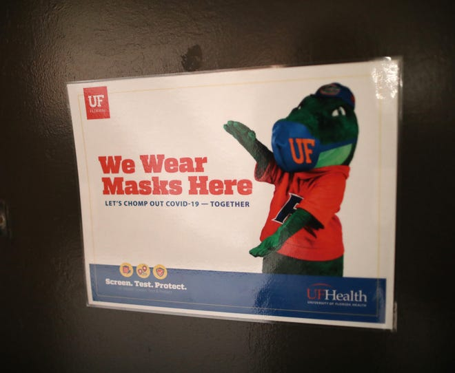 A sign on a classroom door telling anyone who enters to wear a mask, at Weimer Hall on the University of Florida campus, in Gainesville. University of Florida students have been wearing masks on campus since students returned to some on-campus classes in August.