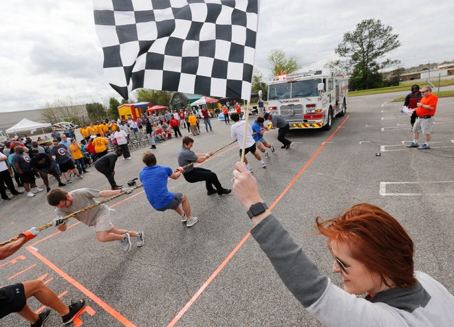 Caroline Railsback is poised with the checkered flag as a team pulls a fire engine during the Pullin' for the Arc fundraising competition behind University Mall Saturday, March 24, 2018. Participants pulled Tuscaloosa Fire and Rescue Engine 5 in a timed competition to determine which team was the fastest and which team was the slowest. [Gary Cosby Jr./Staff Photo]