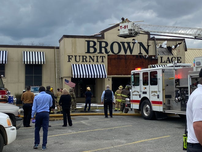 People stand outside Brown's Furniture Showplace on Monday afternoon after a fire began in the façade. The inside of the store was not damaged by fire, according to Alexandria Fire Department Chief Larry King.
