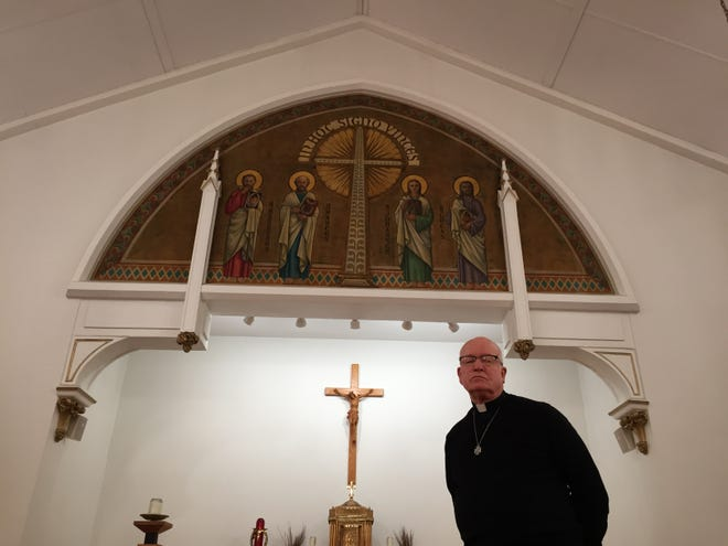 Father Charles Ranges stands inside Holy Family Catholic Church in Essex Junction on March 19, 2021.