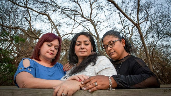 From left: Delia Ramos, Betty Fuentes and Ana Flores Arguelles embrace in prayer in Harlingen. The trio lost their husbands to COVID-19.