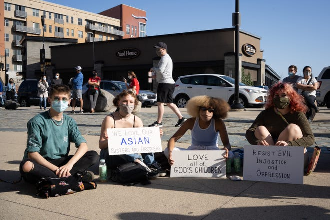 """Henry Chemero, of Wyoming, Tobie Brooks, of College Hill, Fatou Reed, of Northside, and Tuula Lentz, of Northside, sit and wait for a 'Stop Asian Hate,' rally to begin, Sunday, March 21, 2021 at The National Underground Railroad Freedom Center in Cincinnati, Ohio. """"We went to show support during the Black Lives Matter protests over the summer,"""" said Reed. """"So we wanted to do the same thing here. """""""