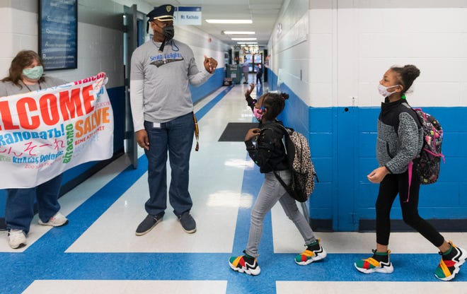 South Heights Elementary teachers Lisa Stone, left, and Anthony Melvin greets students Aryia Gills, center, and Nemyah Hurley, right, as they head to class in Henderson, Ky., Monday morning, March 22, 2021. Monday was the first day the entire student body could be present for in-person instruction since school closures at the beginning of the COVID-19 pandemic in March of 2020.