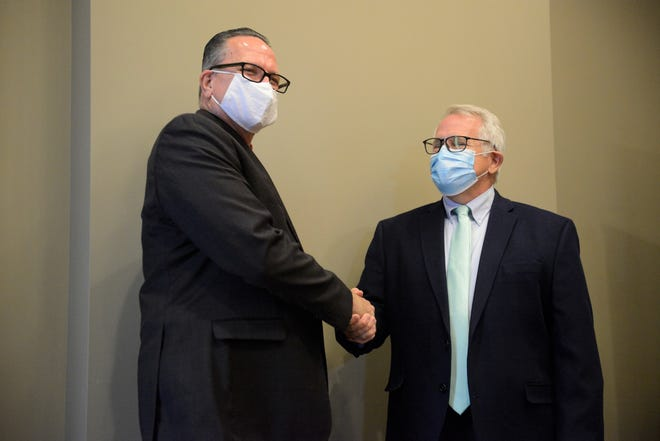 Ontario Mayor Randy Hutchinson and Mansfield Mayor Tim Theaker shake hands after signing a new contract in which Mansfield will continue treating Ontario's wastewater.