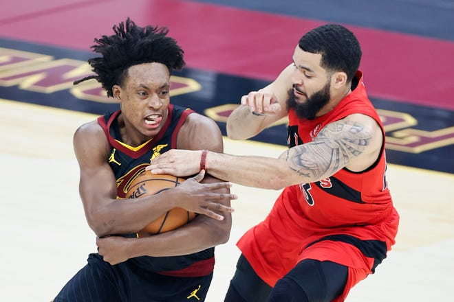 Cleveland Cavaliers' Collin Sexton (2) and Toronto Raptors' Fred VanVleet (23) battle for a loose ball in the first half of an NBA basketball game, Sunday, March 21, 2021, in Cleveland. [Ron Schwane/Associated Press]
