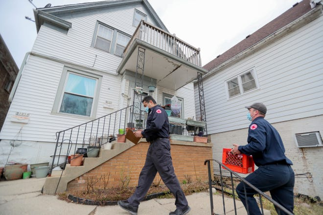 Milwaukee firefighters go door to door to make sure residents have working smoke detectors on Monday in the 3100 block of South 15th Place. A 25-year-old man died Saturday morning after a house on the block that didn't have smoke alarms caught fire.