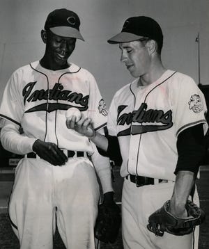 """Satchel Paige, left, and Bob Feller talk over pitching in this photo from July 1948 at Cleveland Municipal Stadium, not long after Paige, then 42, joined the Indians as a 42-year-old rookie. The future Hall of Famers, whose lives intersected frequently over the course of their careers, are part of the focus of """"Our Team: The Epic Story of Four Men and the World Series That Changed Baseball."""""""
