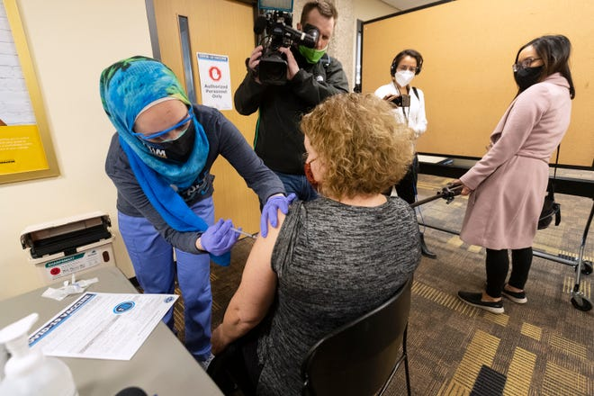 Surrounded by journalists, student nurse Tala Fuad Hatem Abu Zahra administers a first dose of the Pfizer COVID-19 vaccine to Kathy Vance at a vaccination clinic Monday at the University of Wisconsin-Milwaukee.