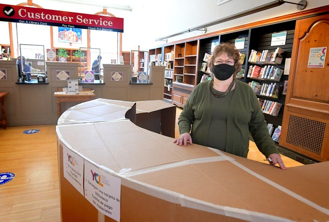 Mina Edmondson, Martin Library director, stands at a prototype of the service desk at the library, Monday, March 22, 2021, while talking about a $10 million expansion project slated for Martin and other county libraries. Bill Kalina photo