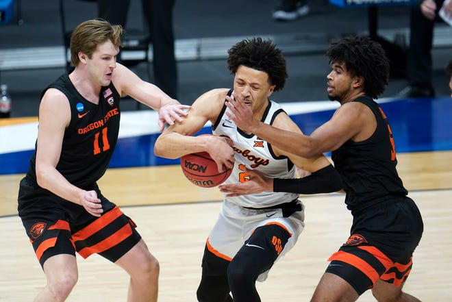 Oklahoma State guard Cade Cunningham (2) drives between Oregon State guard Zach Reichle (11) and Ethan Thompson (5) during the first half of a men's college basketball game in the second round of the NCAA tournament at Hinkle Fieldhouse in Indianapolis, Sunday, March 21, 2021.