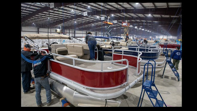 Boats get attention from workers at Tracker Boat's new manufacturing plant in Bolivar. Bass Pro said the new plant adds 250 jobs.