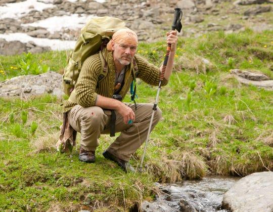 Les Stroud crouches near a stream.