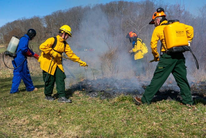 Zane State College wildlife conservation students practice controlling fire set to a small patch of grass prior to the prescribed fire.