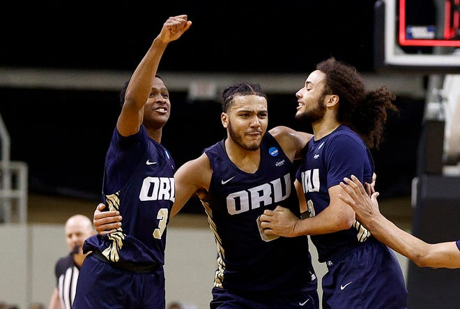 Max Abmas, Kevin Obanor, and Kareem Thompson of the Oral Roberts Golden Eagles celebrate after defeating the Florida Gators.