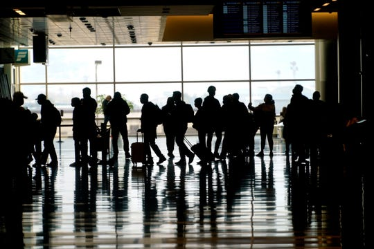 Travelers pass through the Salt Lake City International Airport on March 17. The travel industry is pushing the White House to draw up a plan in the next five weeks to help boost international travel and eliminate COVID-19 restrictions.