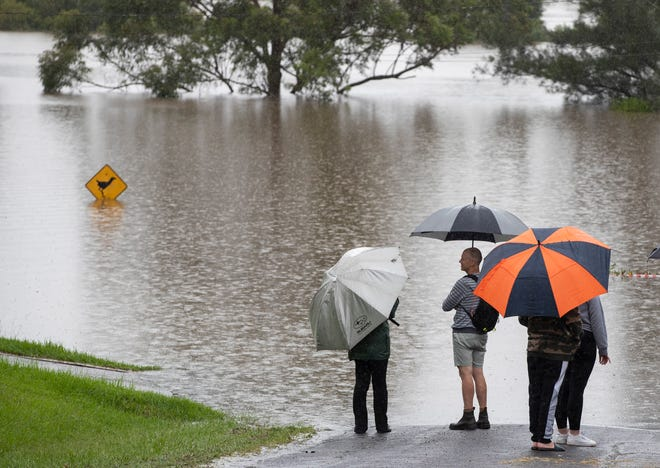 People stand on a flooded road near the Hawkesbury River at Richmond on the western outskirts of Sydney, Australia, on March 22, 2021.