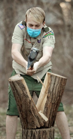 Dominic Summers of Boy Scout Troop 172 demonstrates to fellow members how to properly split firewood Monday in Munroe Falls. The troop recently raised more than $10,000 on GoFundMe to replace all of the camping gear and their trailer after it was stolen earlier this month.