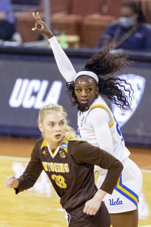 UCLA forward Michaela Onyenwere, top, celebrates after scoring a 3-point basket over Wyoming forward Dagny Davidsdottir during the Bruins' win in the first round of the women's NCAA Tournament at the Frank Erwin Center on Monday. Onyewere moved into a tie for fifth place on UCLA's career scoring list after scoring 25 points in the victory.
