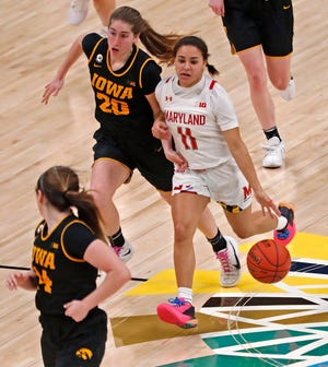 Maryland guard Katie Benzan drives past Iowa's Kate Martin during the Terrapins' win in the Big 10 Tournament on March 13. Benzan leads the country in three-point shooting this season.