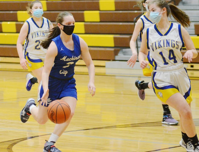 Mackinaw City guard Gabi Bell (left) drives to the basket during the first half of their district semifinal meeting with Alanson Monday, as Vikings senior Kaylynne Costello defends.
