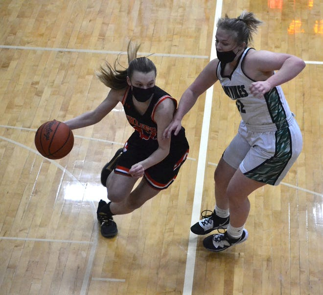 Cheboygan junior guard Olivia Chamberlain (left) drives past Grayling guard Trinity Dutton during the first half of a Division 2 district first-round girls basketball contest in Cheboygan on Monday.