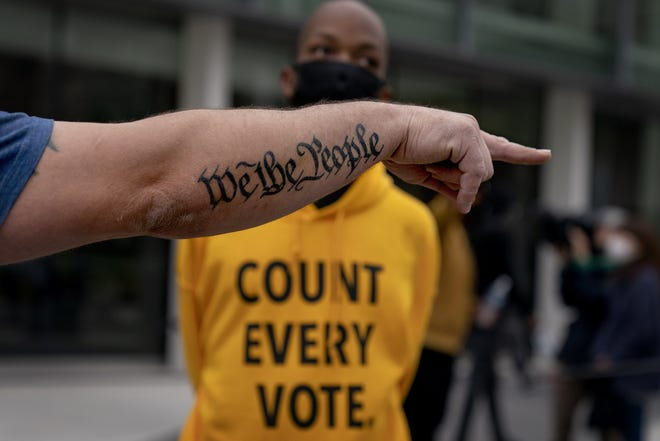 """In this Nov. 5, 2020, file photo, the tattoo """"We The People"""", a phrase from the United States Constitution, decorates the arm of Trump supporter Bob Lewis, left, as he argues with counter protestor Ralph Gaines while Trump supporters demonstrate against the election results outside the central counting board at the TCF Center in Detroit.  (AP Photo/David Goldman, File)"""