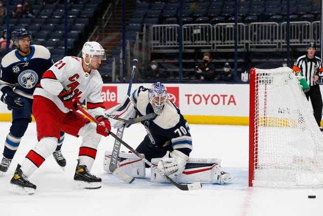 Columbus Blue Jackets' Joonas Korpisalo, right, sweeps the puck away from Carolina Hurricanes' Nino Niederreiter during the third period of an NHL hockey game Monday, March 22, 2021, in Columbus, Ohio. The Hurricanes beat the Blue Jackets 3-0. (AP Photo/Jay LaPrete)