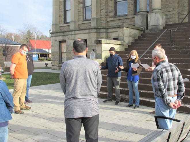 The Rev. Rachelle Lyndaker Schlabach, of Millersburg Mennonite Church, reads a passage from Psalm 6 during a prayer vigil on the square outside the Holmes County Courthouse Tuesday evening, as a small group gathers to remember the Asian Americans killed last week in Georgia.