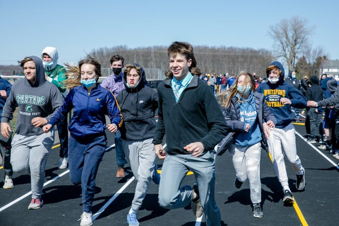 Whiteford freshman Hunter DeBarr (middle) and classmates, celebrate the official opening of the new Whiteford Agricultural Schools track Friday, March 19, by taking a victory lap on the new 8-lane, all-weather track.