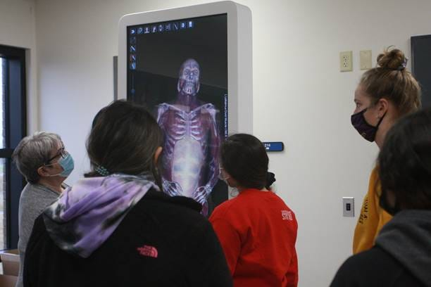 Mary Scott (left), DCCC professor of biology, demonstrates the college's new Anatomage virtual cadaver table during an anatomy and physiology lab on Tuesday, March 23.