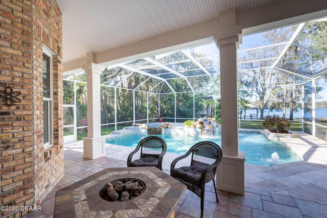 The screened-in outdoor area of this New Smyrna Beach home features a spacious lanai, with a heated saltwater pool and Jacuzzi, with a rock waterfall, surrounded by a Travertine pool deck.