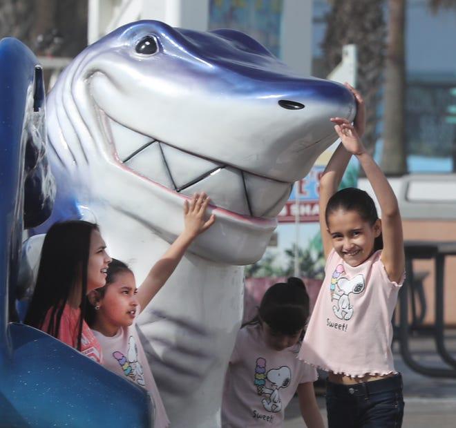 Children play on the big fiberglass shark on the Daytona Beach Pier this spring as beachgoers returned for another season.
