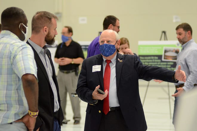 """The Ascension Parish Council's John Cagnolatti talks to fellow council members Alvin """"Coach"""" Thomas and Joel Robert at the first sewer proposal open house event in Donaldsonville."""