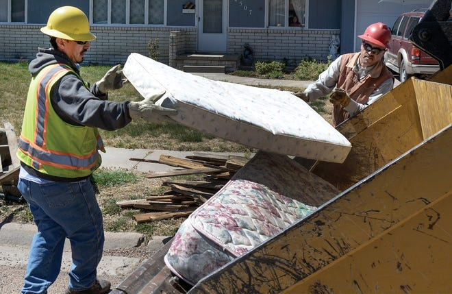 City workers Mario Saucedo, left, and Roque Flores move a mattress in to the bucket of a front loader for disposal in the 500 block of North Sixth Street. This year's event will be from March 29 through April 9.
