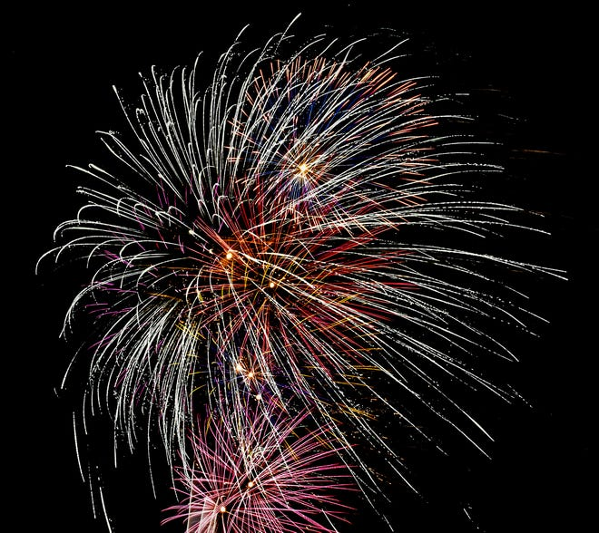 Fireworks light up the sky as the wind stretches their shapes July 4 during Garden City's annual fireworks display originating in the Arkansas River bed area.