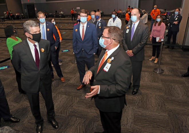 Dan Drake, right, president of Vidant Medical Center, leads Gov. Roy Cooper, left, and a group of other leaders on a tour of the Vidant/Pitt County large-scale COVID-19 vaccine clinic at the Greenville Convention Center March 19 in Greenville, N.C. (Deborah Griffin/The Daily Reflector via AP)