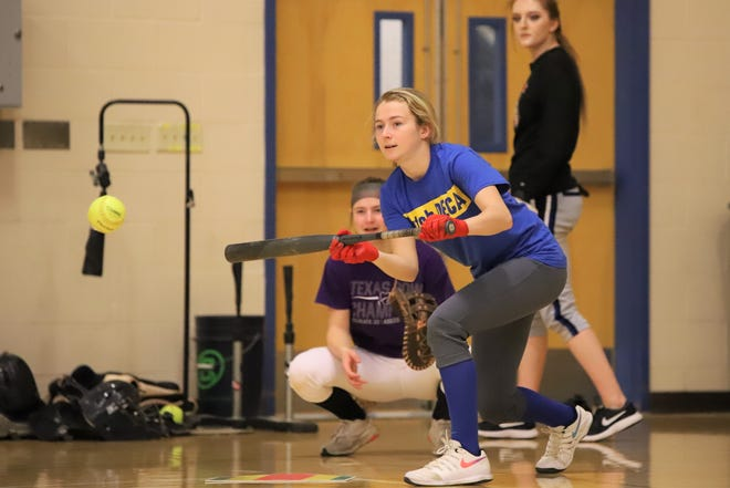 Hutchinson High outfielder Emilee Railsback executes a bunt during indoor practice at Hutchinson High School.