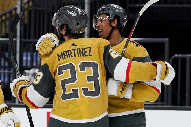 Vegas Golden Knights right wing Keegan Kolesar, right, celebrates with defenseman Alec Martinez (23) after defeating the St. Louis Blues in an NHL hockey game Monday, March 22, 2021, in Las Vegas.