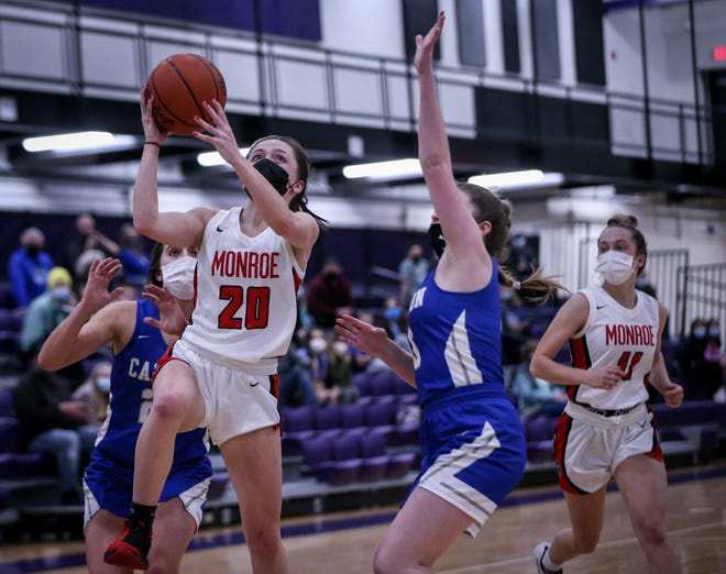 Monroe's Olivia Bussell (20) drives to the basket past Gibraltar Carlson's Emma Shimizu (24) and Rachael Poli (5) during the third quarter Monday, March 22, 2021 in the Division 1 District opener at Woodhaven. Coming in behind the play is Monroe's Ellie Sieler.