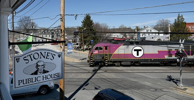 A commuter rail train passes through downtown Ashland as seen from the balcony of Stone's Public House, March 23, 2021. The Irish pub dates to 1834, when businessman John Stone built his hotel just a few feet away from the railroad tracks.