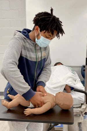 Crestview High School junior Savion Harris demonstrates the CPR technique he used recently to help save a 6-month-old child who was not breathing. Harris learned CPR in one of his classes in the school's Career Technical Education curriculum.