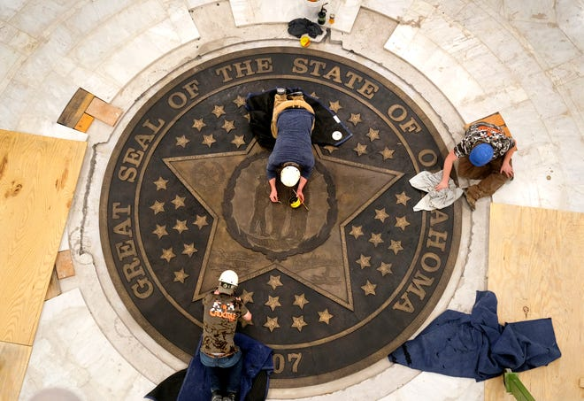 Workers from The Crucible in Norman, put the finishing touches on the new Seal of the State of Oklahoma in the ground floor of the Capitol as part of widespread building renovations, Monday, March 22, 2021.