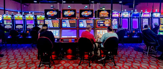 Patrons stay spaced out as they play games May 11 at the Thunderbird Casino for its soft reopening in Norman.