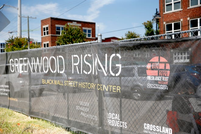 A screen hangs on a fence during a groundbreaking for the Greenwood Rising Black Wall Street History Center in Aug. 2020.