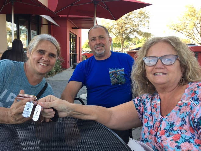 """From left, Debby, James and Mylaen Merthe.  The women hold tags that say """"Kidney recipient/I run on spare parts."""" Debby and James married on Nov. 22; two days later, Debby served as living kidney donor to Mylaen, who is James' ex-wife."""